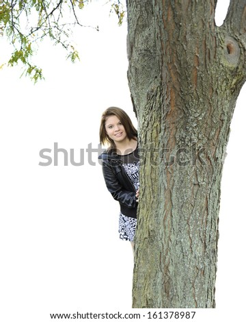 A beautiful young teen smiling at the viewer from behind a large tree.  Isolated on white. - stock photo