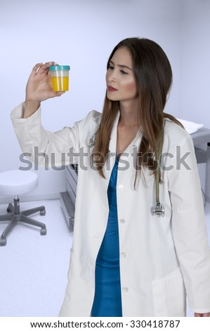A beautiful young woman doctor holding a urine sample - stock photo