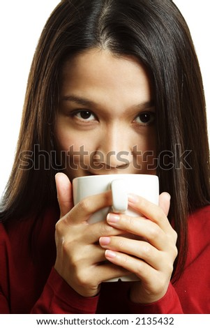 A beautiful young woman drinking a hot cup of coffee - stock photo
