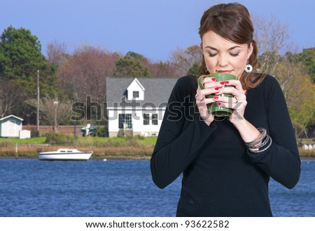 A beautiful young woman drinking and smelling coffee in her pajamas - stock photo