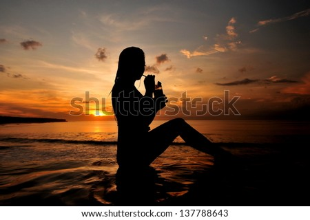 a beautiful young woman drinking cocktail on the beach at sunset on background - stock photo