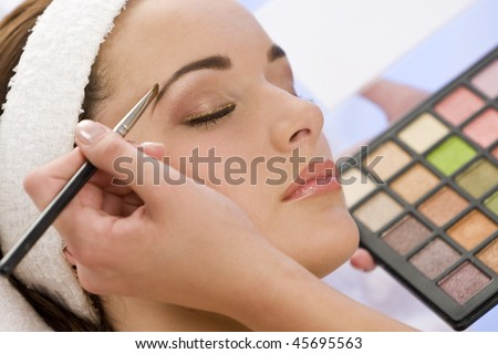 A beautiful young woman having her make up applied by a beautician in health spa. - stock photo