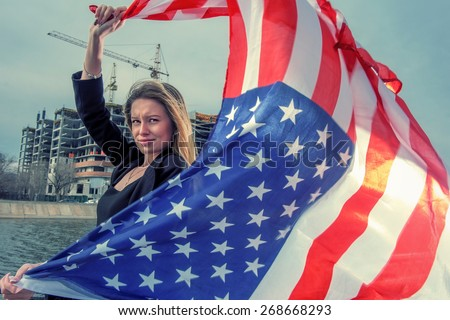 A beautiful young woman holding an American flag fly by wind against building development scene - stock photo