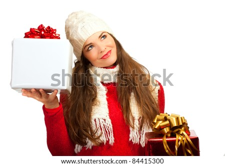 A beautiful young woman holding two Christmas gifts and looking contemplative. - stock photo