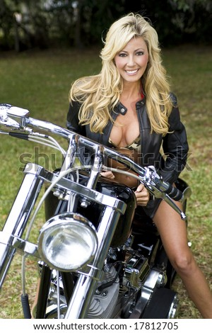 A beautiful young woman in a bikini and leather jackets sitting on a black and chrome motorbike - stock photo