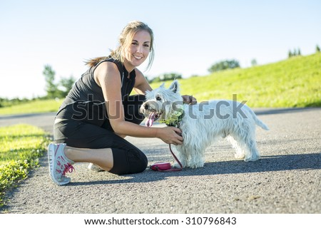 A Beautiful young woman jogging with her dog - stock photo