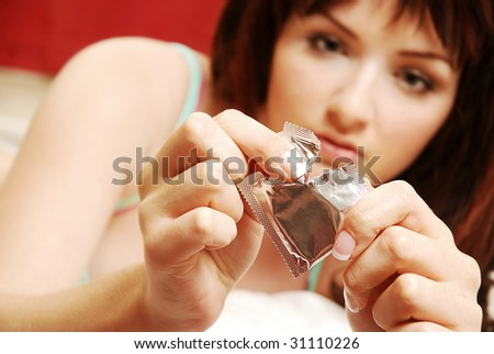 A beautiful young woman opening a condom on her bed. Focus on the condom in the foreground. - stock photo