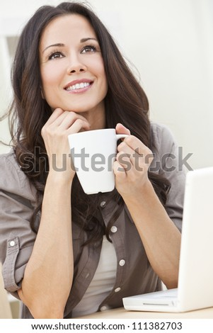 A beautiful young  woman or girl with a wonderful enigmatic smile using laptop computer or pc while drinking tea or coffee from a white cup at home - stock photo