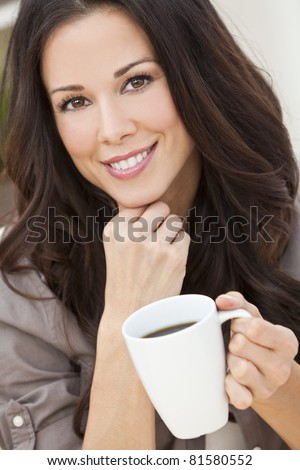 A beautiful young woman or girl with a wonderful smile drinking tea or coffee from a white cup - stock photo