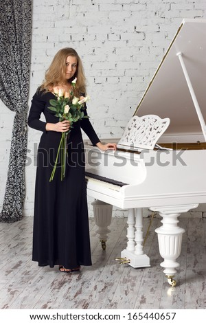 A beautiful young woman playing piano - stock photo