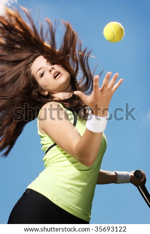 A beautiful young woman playing tennis. Action shot. - stock photo