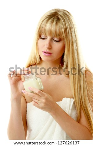 A beautiful young woman putting cream on her skin - stock photo