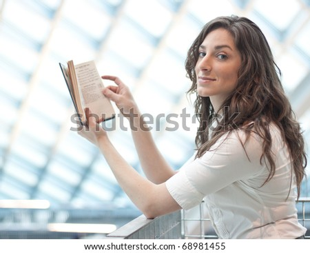 A beautiful young woman reading a book with a modern library in background - stock photo