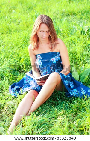 A beautiful young woman sitting on the green grass and reading a book - stock photo