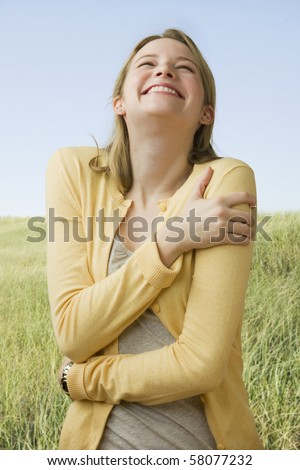 A beautiful young woman stands in a grass field while laughing.  Vertical shot. - stock photo