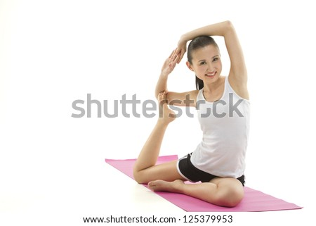 A beautiful young woman stretching on a pink yoga mat - stock photo