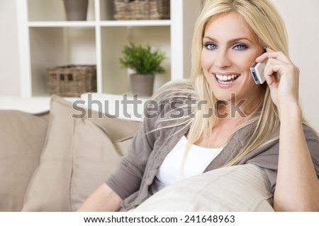 A beautiful young woman talking on her cell phone at home - stock photo