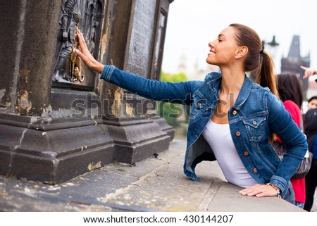 a beautiful young woman touching the bronze plaque on charles bridge for good luck - stock photo