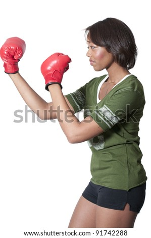 A beautiful young woman wearing a pair of boxing gloves - stock photo