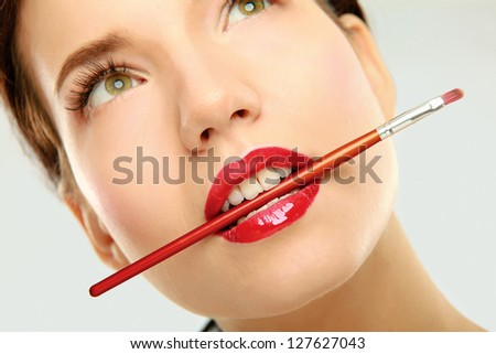 A beautiful young woman wearing red lipstick and biting a makeup brush - stock photo