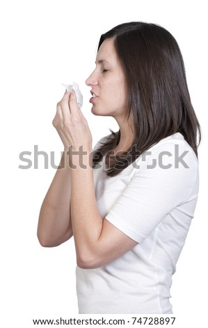 A beautiful young woman with hay fever allergies blowing her nose. - stock photo