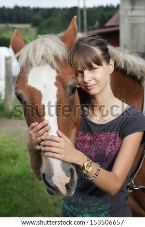 A beautiful young woman with her pony in the paddock, looking at camera - stock photo
