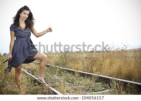 A beautiful young woman with long brown hair,wearing a blue dress, standing with one leg on the rail road and hitchhiking - stock photo