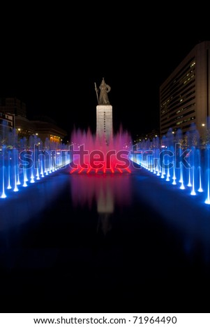 A beautifully colored red blue water fountain illuminates the front of the centered historic Admiral Yi Sun Sin statue at night in downtown Seoul, South Korea. Vertical copy space - stock photo
