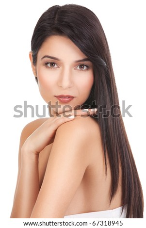 a beauty portrait of a young woman, shot on white background. she has long, dark brown hair; she looks over her shoulder, touching it with her hand. - stock photo