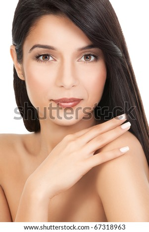 a beauty portrait of a young woman, shot on white background. she has long, dark brown hair; she looks over her shoulder smiling, while she is touching it with her hand. - stock photo