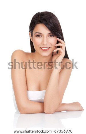 a beauty portrait of a young woman, smiling, shot on white background.  she rests her arms on a white table and touches her face delicately with her fingers - stock photo