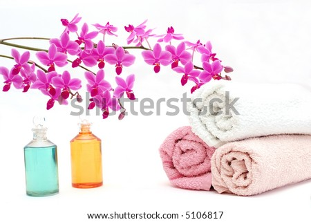 A beauty set with towels, body oil and a beautiful orchid. - stock photo