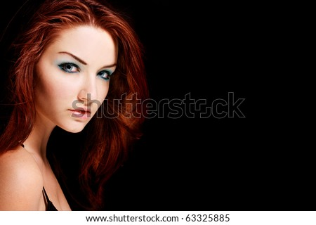 A beauty shot of a young blue eyed woman with her red hair looking at the camera. - stock photo