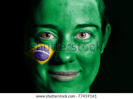 A beauty woman with the Flag of Brazil painted on her face - stock photo