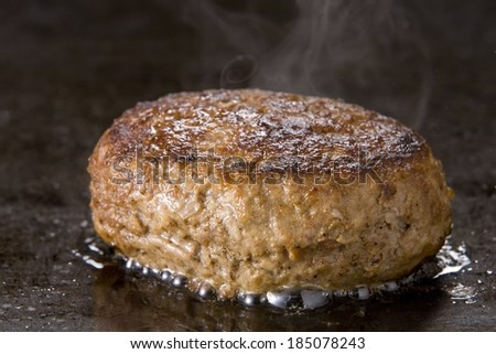 A beef burger patty cooking on a grill. - stock photo