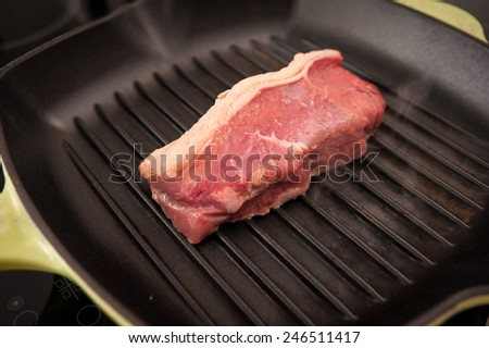 a beef rump steak cooking in a grill pan - stock photo
