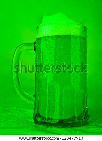 A beer mug of green beer with a foamy head on a green background - St. Patricks Day theme - stock photo
