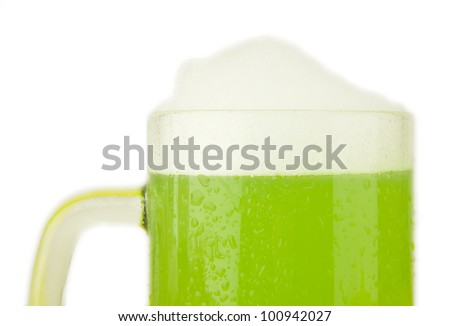 A beer mug of green beer with a foamy head on a white background - St. Patricks Day theme - stock photo