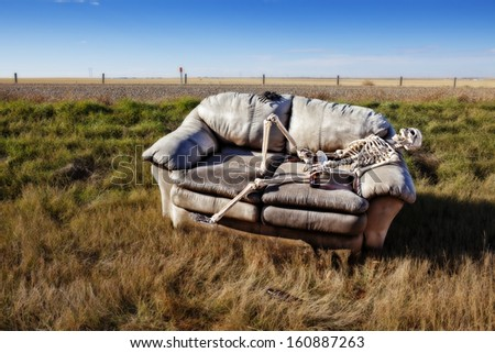 A beer stained party couch haunted by parties past, discarded in a ditch on a rural prairie road. - stock photo