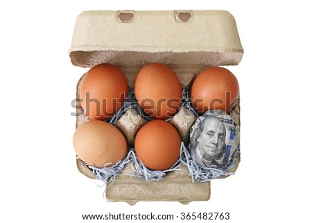 A beige paper pulp egg tray package made of recycled paper full of fresh chicken eggs with one wrapped in 100 US dollar banknotes - stock photo