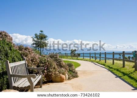 A bench and sidewalk in a public park along the coast in Santa Barbara, California. - stock photo