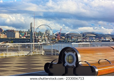 A bench at the Pier 66 with panorama of Puget Sound shore in Seattle, USA. Late afternoon sun touched piers along Alaskan Way in Seattle downtown. - stock photo