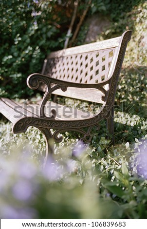 A bench in a garden. - stock photo