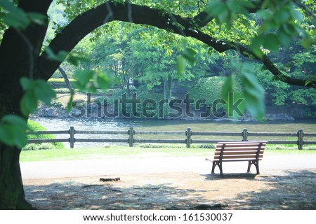 A bench in a park with a lake and a fence. - stock photo