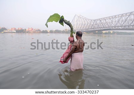A Bengali man carries Kala Bou (banana plant ) for holy dip in river Ganges on occasion of Durga Puja festival on October 20, 2015 in Calcutta, India. - stock photo