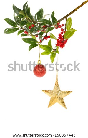 A berry laden holly bough decorated with a Christmas star and bauble - stock photo