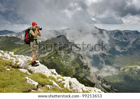 a beutiful young girl takes pictures above the clouds on the Maglic Peak, Bosnia and Herzegovina - stock photo