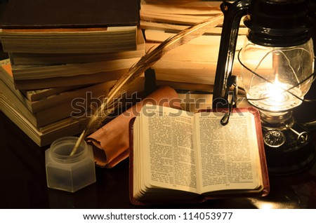 a bible surrunded by books in a lamp light - stock photo