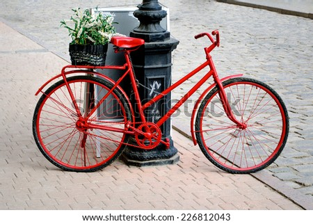 a bicycle is red with the small basket of colors - stock photo