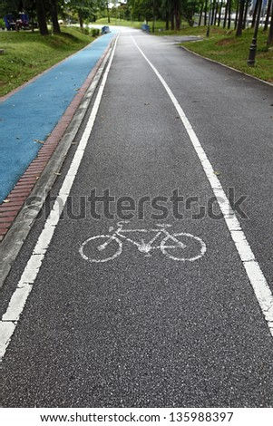 A bicycle lane and a blue rubberized jogging path through a green outdoor recreational park. - stock photo